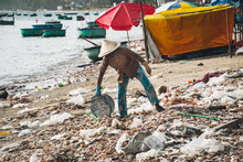 Vietnamese Woman Throws Garbage On The Beach By The Sea. Dump By The Sea. Bad Ecology In Southeast Asia. Fishermen Village In MUI Ne