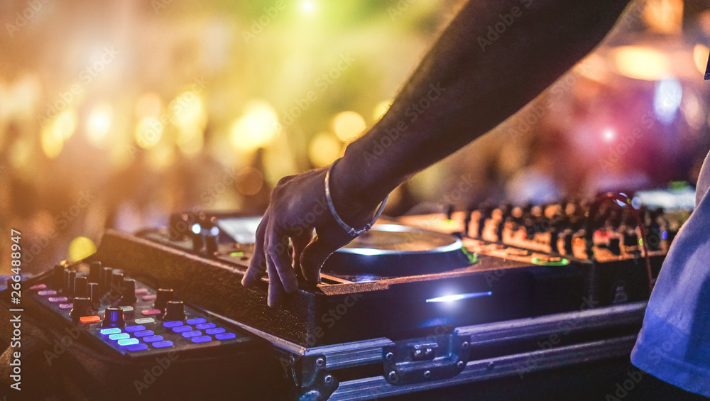 Fototapeta Dj mixing outdoor at beach party festival with crowd of people in background - Summer nightlife view of disco club outside - Soft focus on hand - Fun ,youth,entertainment and fest concept