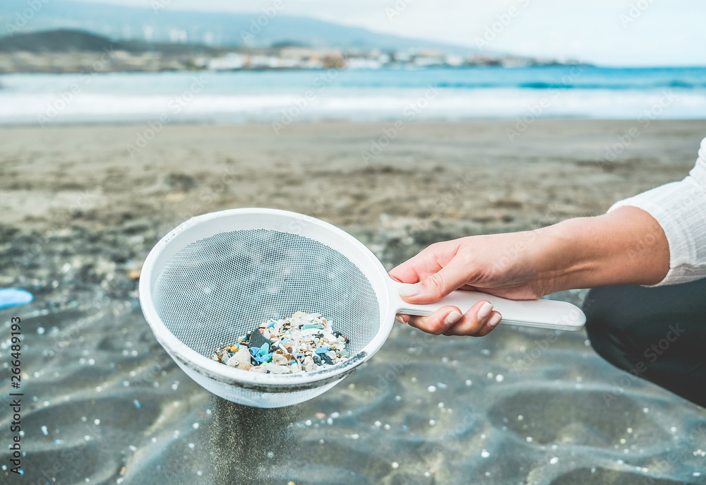 Fototapeta Young woman cleaning microplastics from sand on the beach - Environmental problem, pollution and ecolosystem warning concept - Focus on hand