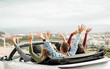 Happy friends with hands up having fun in convertible car on summer vacation - Young people laughing and smiling together during travel holidays - Youth lifestyle concept - Main focus on guys heads