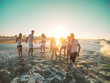 canvas print picture - Happy friends having fun on the beach at sunset - Young people playing inside sea water outdoor in summer vacation - Friendship, youth, travel concept - Soft focus on right guys