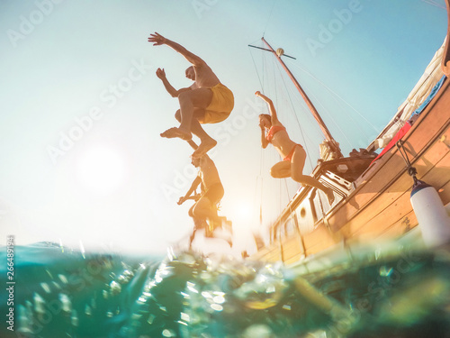 Happy friends diving from sailing boat into the sea - Young people jumping insid Wallpaper Mural