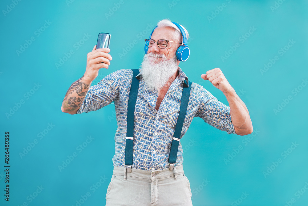 Fototapeta Senior hipster man using smartphone app for creating playlist music - Trendy tattoo guy having fun with mobile phone technology - Tech and joyful elderly lifestyle concept - Focus on his face