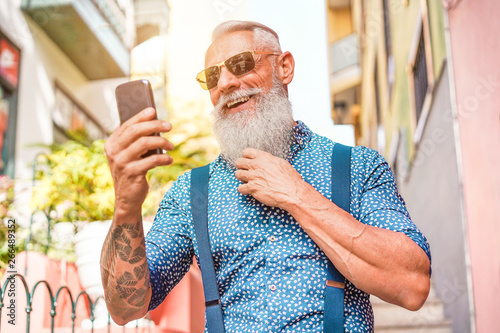 Obraz Trendy senior man using smartphone app in downtown center outdoor - Mature fashion male having fun with new trends technology - Tech and joyful elderly lifestyle concept - Focus on his face - fototapety do salonu