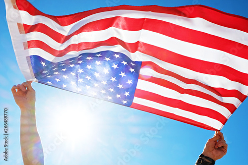 Close up shot of man hands holding United State of America flag waving on the wind, clear blue sky Wallpaper Mural
