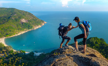 Man And Woman Hiking On The Top Of Cliff In Summer Mountains At Morning Time And Enjoying View Of Nature