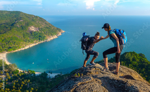Fototapeta Man and woman hiking on the top of cliff in summer mountains at morning time and enjoying view of nature obraz