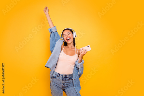 Close up photo beautiful she her model lady trendy earflaps eyes closed overjoyed sunny day good playlist telephone wear casual pastel tank-top jeans denim jacket isolated yellow bright background - 266492327