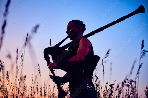Foto A young modern man plays musical bagpipes outside. Siluet