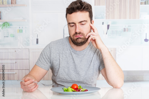 Fotografija  Worried man hungry and starved with salad