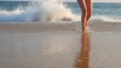 Legs of young woman walking from the ocean waves to the sand beach. Feet of unrecognizable girl in bikini stepping from the sea to shore. Summer vacation or holiday. Concept of rest. Slow motion