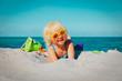 Leinwandbild Motiv cute little girl play with sand on beach