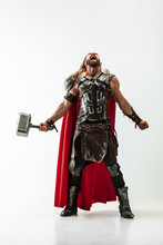 Long Hair And Muscular Male Model In Leather Viking's Costume With The Big Hammer Cosplaying Thor Isolated On White Studio Background. Full-lenght Portrait. Fantasy Warrior, Antique Battle Concept.