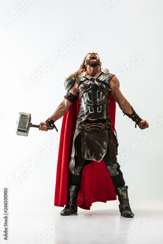 Leinwand Poster Long hair and muscular male model in leather viking's costume with the big hammer cosplaying Thor isolated on white studio background