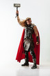 Leinwanddruck Bild Long hair and muscular male model in leather viking's costume with the big hammer cosplaying Thor isolated on white studio background. Full-lenght portrait. Fantasy warrior, antique battle concept.