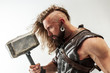 Leinwanddruck Bild God of thunder. Blonde long hair and muscular male model in leather viking's costume with the big hammer cosplaying Thor isolated on white studio background. Fantasy warrior, antique battle concept.