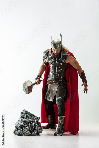 Платно Long hair and muscular male model in leather viking's costume with the big hammer cosplaying Thor isolated on white studio background