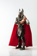 canvas print picture Long hair and muscular male model in leather viking's costume with the big hammer cosplaying Thor isolated on white studio background. Full-lenght portrait. Fantasy warrior, antique battle concept.