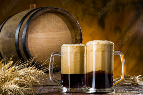 Poster de jardin Nature Dark beer with foam in glasses on a wooden table near the barrel,.rye spikelets