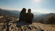 Couple sitting and hugging at a top of a mountain. View from the back.