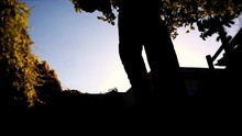 Dark Shadow Silhouette Of Male Figure Closeup Digging Dirt & Throwing It Towards Camera View. Bright Foliage Background. Scary, Creepy Concept Or Gardening, Grave Digger Burial.