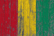 Flag of Guinea painted on worn out wooden texture background.