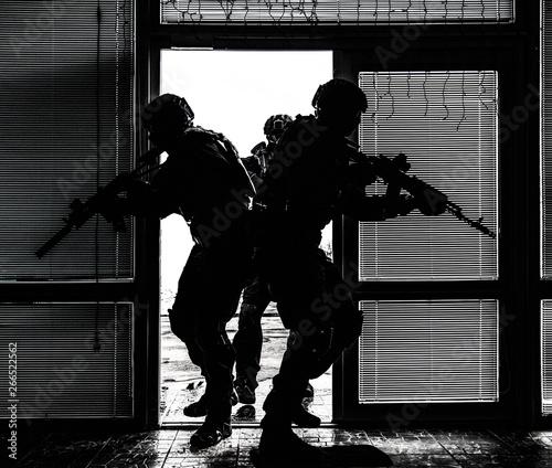 Fotografía SWAT team breaching door and storming apartments