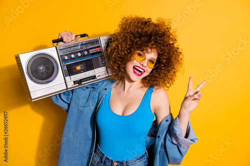 Magasin de musique Close up photo beautiful she her lady wavy fluffy styling curls old-fashioned tape recorder show v-sign wear casual jeans denim shirt shorts tank top outfit clothes isolated yellow bright background