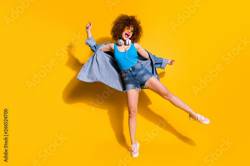 Full length body size photo funky funny she her lady wavy styling clubber amazed excited strange moves wear ear flaps specs casual jeans denim shirt shorts tank top clothes isolated yellow background - 266524700
