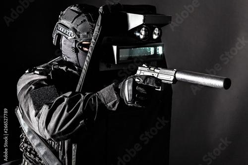 Fotografie, Obraz  Armed SWAT fighter hiding behind ballistic shield