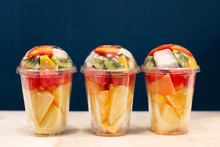 Three Mixed Fruit Vitamin Salad In The Plastic Glass Ready To Takeaway. Kiwi, Pineapple, Watermelon, Coconut, Strawberry, Mango In Plastic Container. Copy Space.