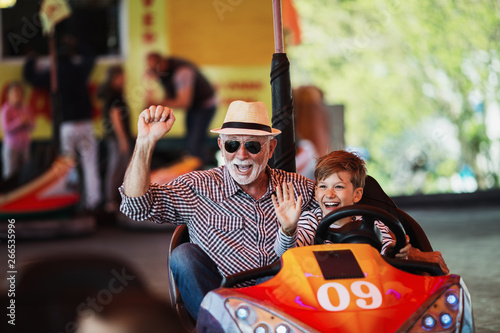 Grandfather and grandson having fun and spending good quality time together in amusement park Canvas Print