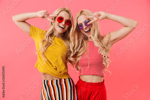 Cadres-photo bureau Kiev Happy blonde twins in sunglasses showing peace gestures