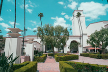 Union Station In Los Angeles California USA. Beautiful Summer Spring Weather Outdoor In America. Forecourt Green Garden Park Trees Of Historical Building With Tall Clock Tower Showing Time Blue Sky.