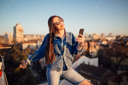 Young woman on the rooftop, taking a selfie during sunset - 266538579