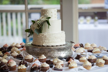 Beautiful Three Tiered Wedding Cake Surrounded By Cupcakes At Wedding Reception.