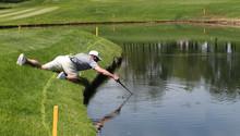 A Golfer Reaches Into A Pond T...