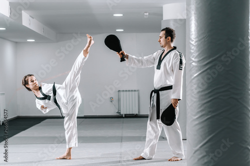 Fototapety, obrazy: Caucasian handicapped highly motivated girl practicing taekwondo with her training. Girl kicking kick target.