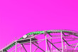 canvas print picture - Green roller coaster with a loop and a bend in an amusement park against a blue sky in neon pink purple color toning. in the style of pop zine culture selective focus. Creative concept.