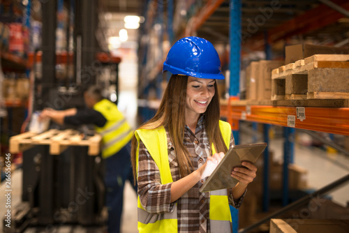 Fotomural  Female warehouse worker holding tablet checking inventory in distribution warehouse