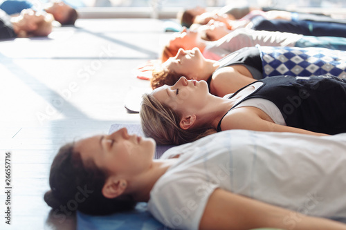 Fotografia  Side view of a young woman lying on a rug on the floor during the performance of shavasana during group yoga classes