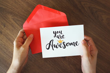 """Hand Holding Red Envelope With """"You Are Awesome"""" Card"""