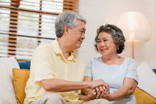Asian Elderly Couple Holding Their Hands While Taking Together In Living Room, Couple Feeling Happy Share And Support Each Other Lying On Sofa At Home. Lifestyle Senior Family At Home Concept.