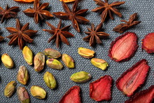 Dried Strawberries Cut Into Pieces To Decorate The Dessert. Nearby Are Pistachios And  Anise. On A Gray Background.