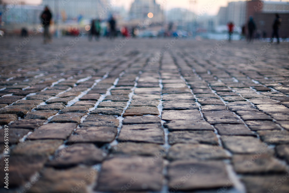 Fototapeta Stone pavement in perspective. Old street paved with stone blocks. Shallow depth of field. Vintage grunge texture.