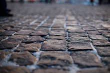 Stone Pavement In Perspective. Old Street Paved With Stone Blocks. Shallow Depth Of Field. Vintage Grunge Texture.
