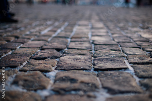 Obraz Stone pavement in perspective. Old street paved with stone blocks. Shallow depth of field. Vintage grunge texture. - fototapety do salonu