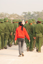 Vietnamese Teenage Girl Walks With A Group Of Young Vietnamese Soldier.