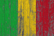 Flag of Mali painted on worn out wooden texture background.
