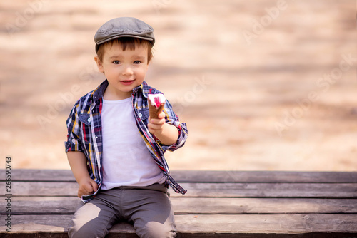 Portrait of fancy toddler child sitting on bench outdoor and holding an ice-cream offering to share dessert with him Canvas Print